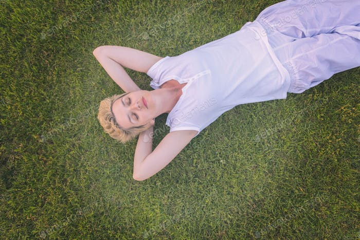 top view of young woman relaxing on the grass