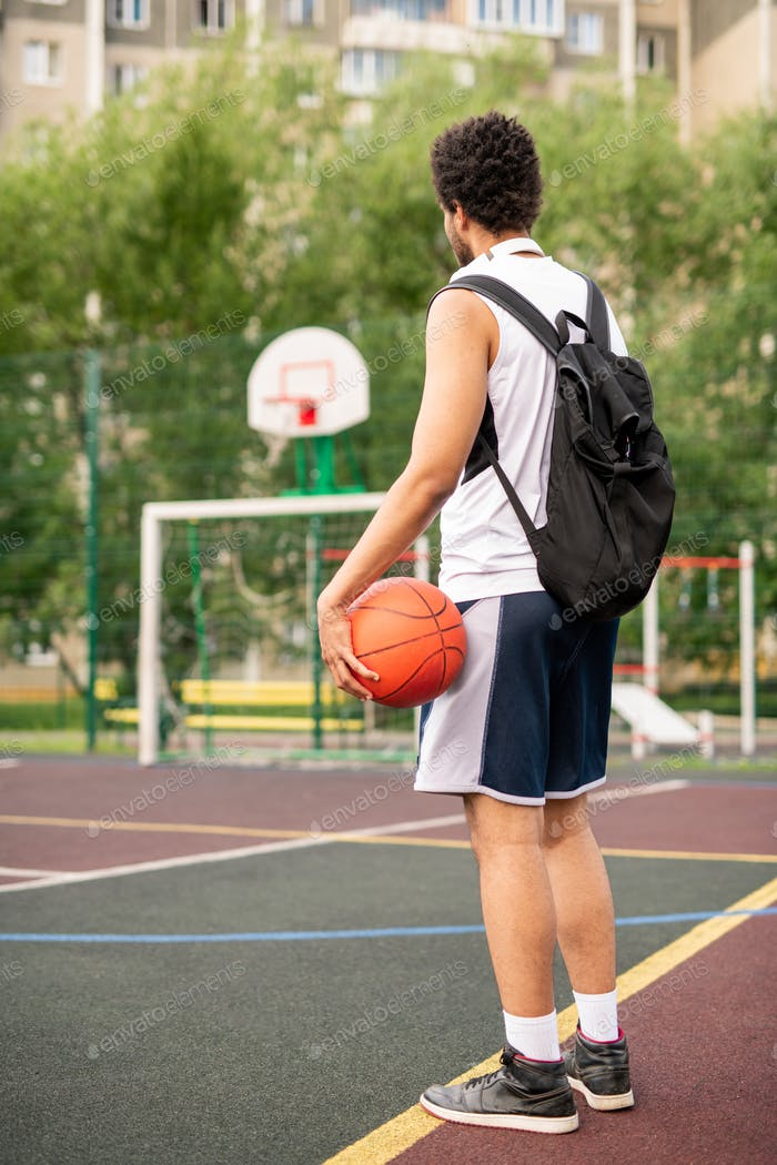Young active male basketball player with ball and backpack on playground