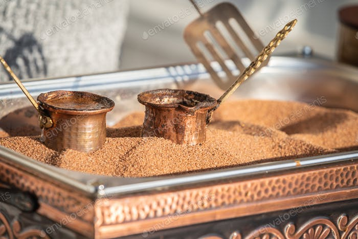 Preparation of Turkish coffee in the cezve in the sand