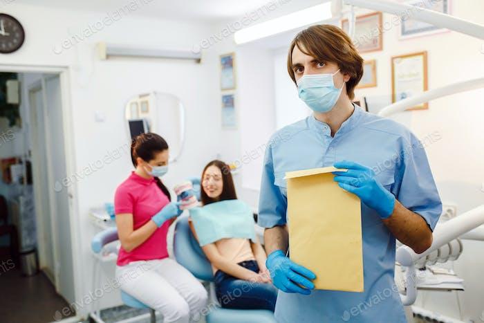 Zahnarzt mit Dokumenten in den Händen
