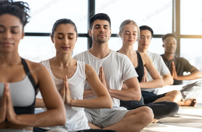 Zen. Multiethnic Group Of Relaxed People Meditating Together In Yoga Studio