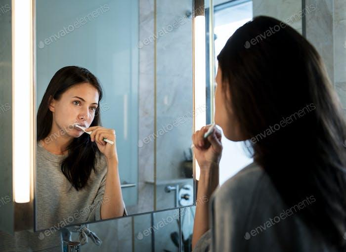 Frau putzt ihre Zähne am Morgen