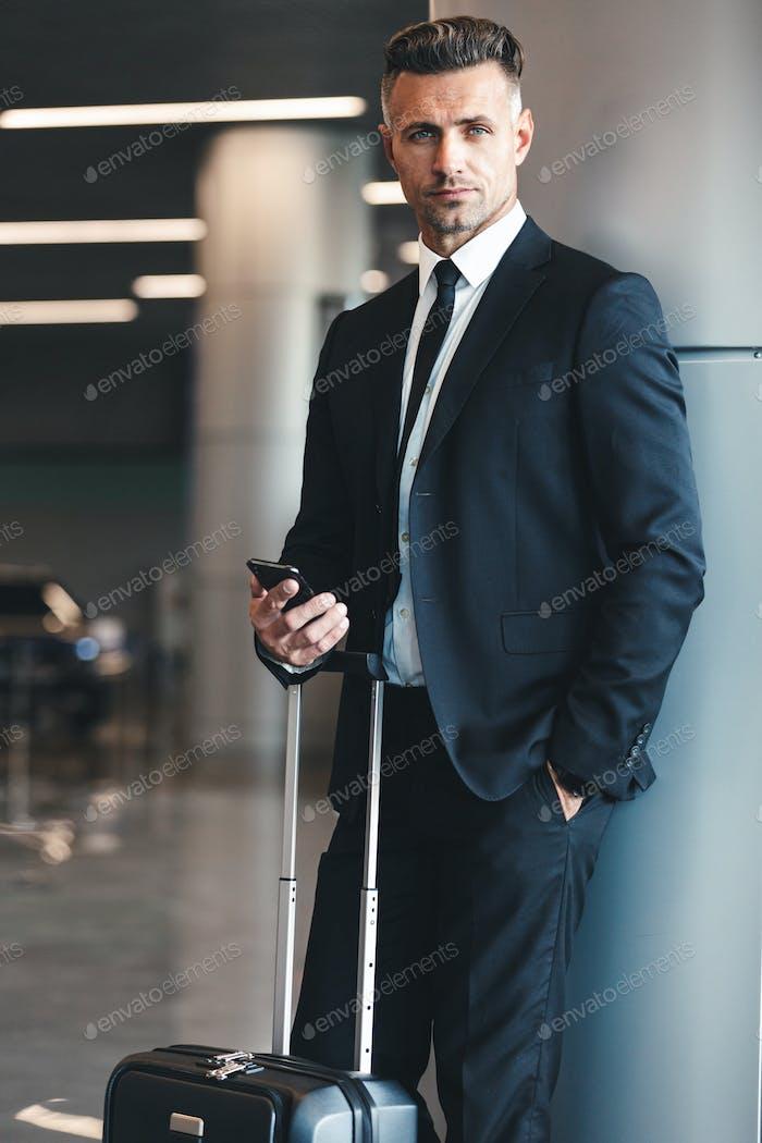 Confident mature businessman holding mobile phone