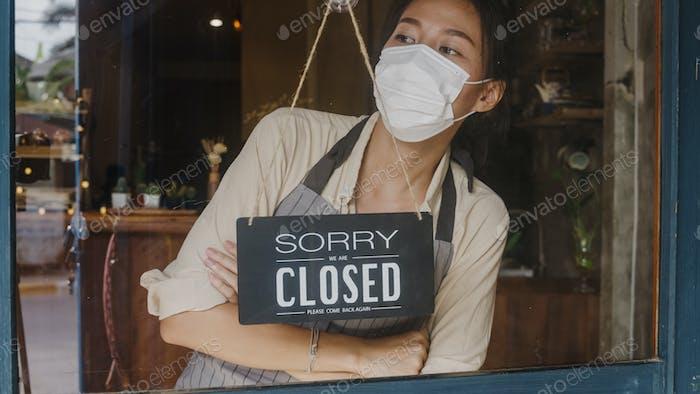 Joven Asia chica usar máscara facial girando un signo de abierto a cerrado signo en la cafetería puerta de vidrio.
