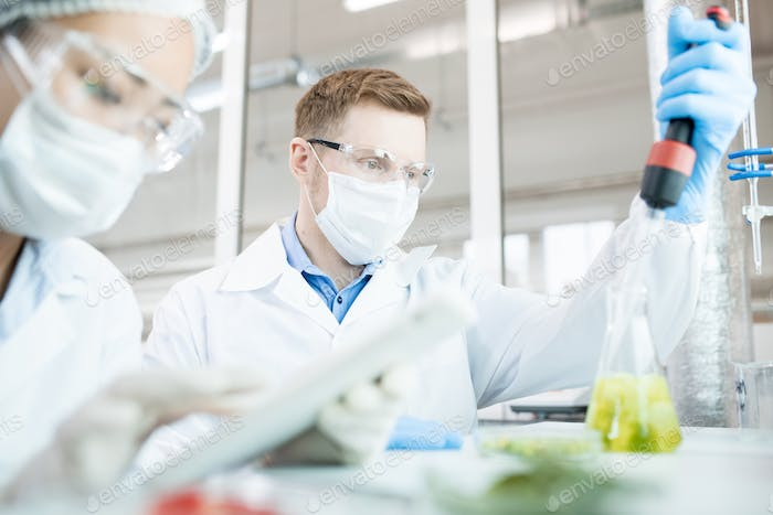 Microbiologist taking sample of solution in flask