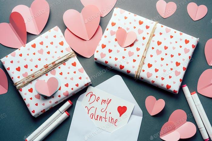 Draufsicht auf Tisch mit Herzen und Geschenkboxen mit Glückwünschen zum Valentinstag.