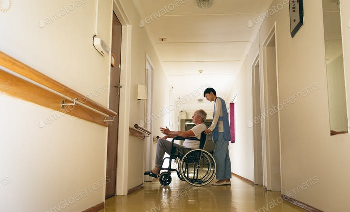Nurse pushing disabled senior male patient sitting in wheelchair in corridor at retirement home