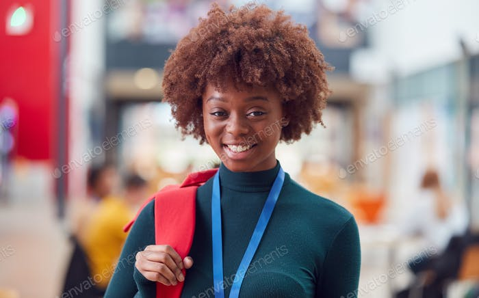 Portrait Of Smiling Female College Student In Busy Communal Campus Building