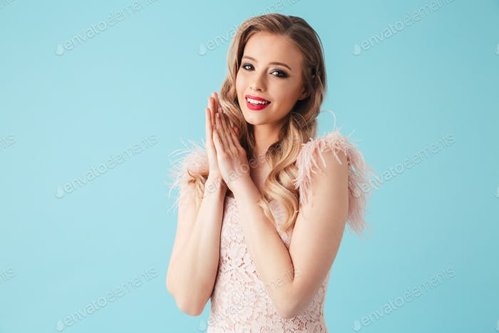 Sensual blonde woman in dress posing with arms near face