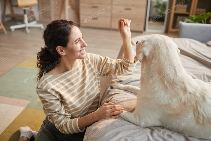 Happy Young Woman Playing with Dog at Home