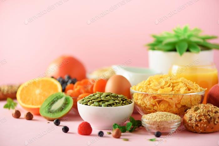 Corn flakes with milk, fresh berries, yogurt, boiled egg, nuts, fruits, orange, banana, peach for