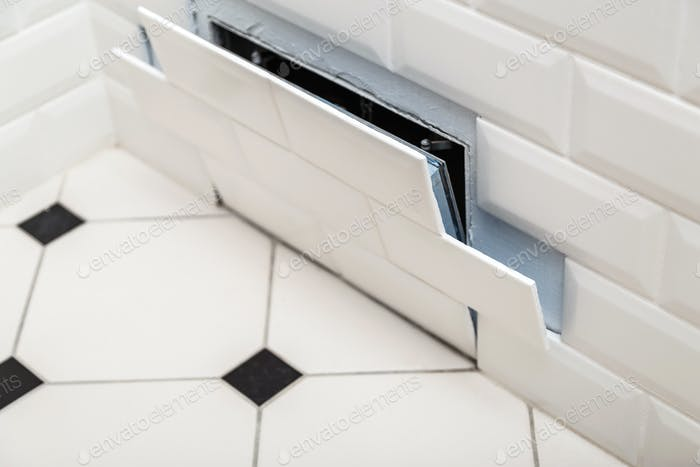 Open hidden revision sanitary hatch on the wall of tile under the bathroom