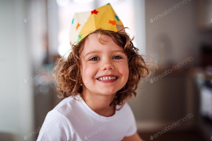 Una niña pequeña con una corona de Papel en Página de inicio, mirando a la cámara.