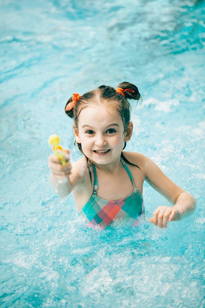 Mädchen in einem Schwimmbad mit einer Wasserpistole