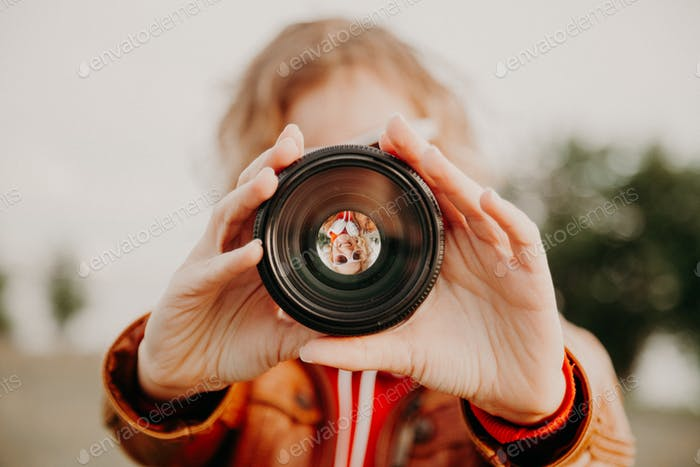 Young woman looking through camera lens. Photography and art concept