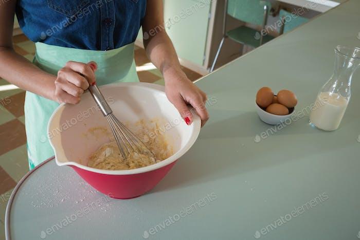 Junge Frau Schneebesen Mischung in Schüssel in der Küche