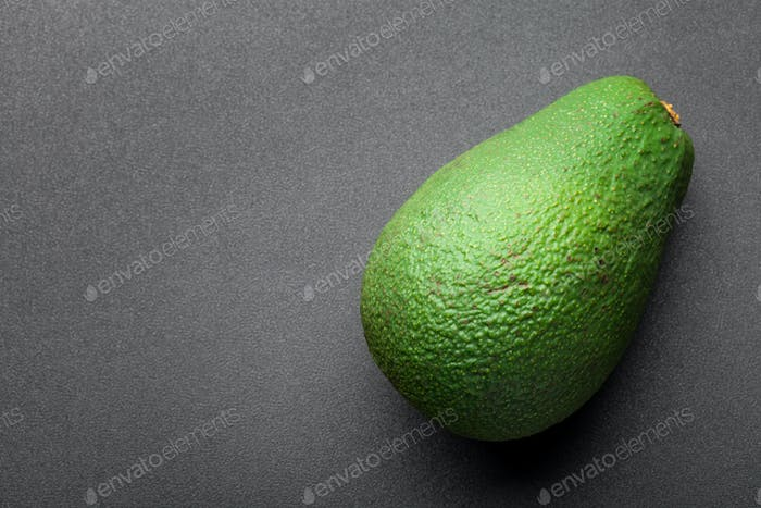 green avocado isolated on dark background. top view