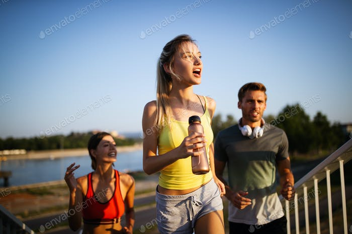 Athletic fit people exercising and running together outdoors
