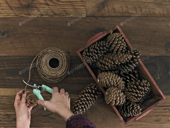 A person using secateurs or cutters on string. A box of pine cones.