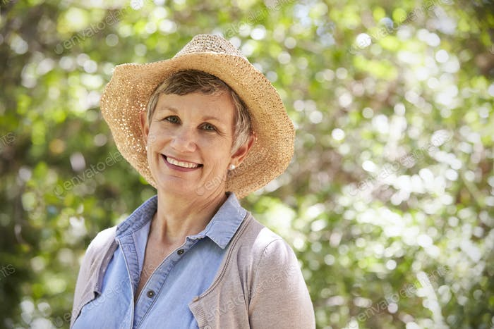 Outdoor Portrait Of Mature Woman Wearing Straw Hat
