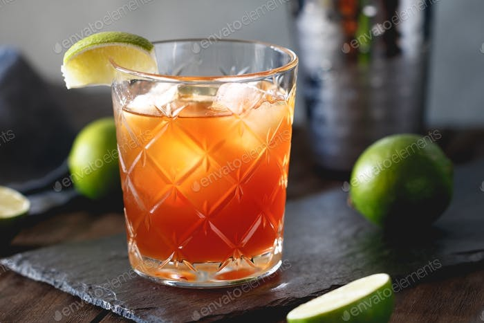 The alcoholic Surfer on Acid cocktail in a old-fashioned glass with a lime wedge.