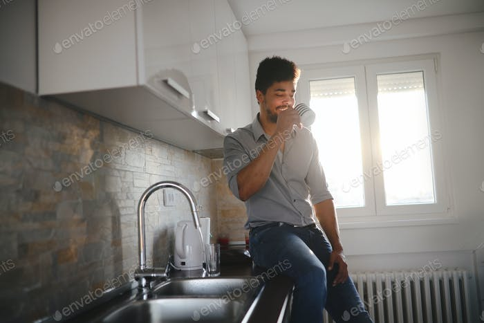 Handsome african american man drinking coffee in kitchen