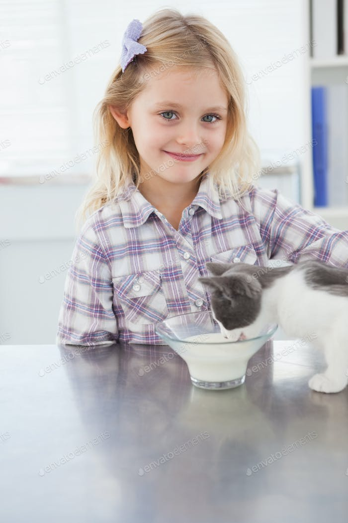 Happy owner petting her cat drinking milk in medical office