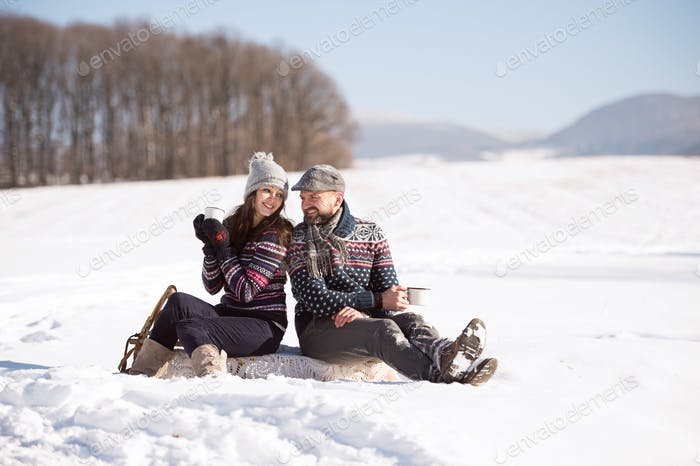 Young woman and man with cup of coffee in winter nature.