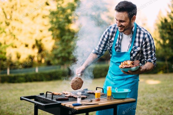 Handsome man preparing barbecue