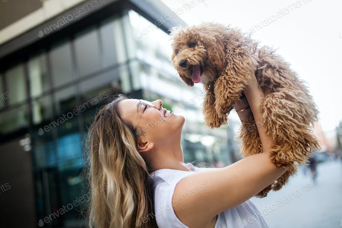 Happy young woman with her dog in the summer