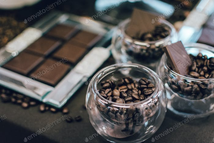 Dark chocolate bar and coffee beans in bowls