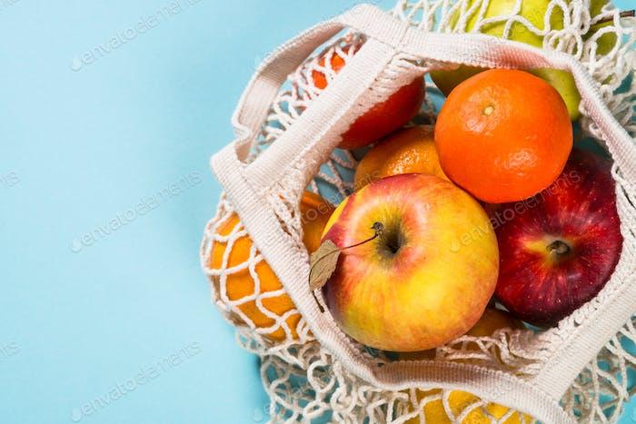 Mesh-Beutel mit Früchten auf farbigem Hintergrund