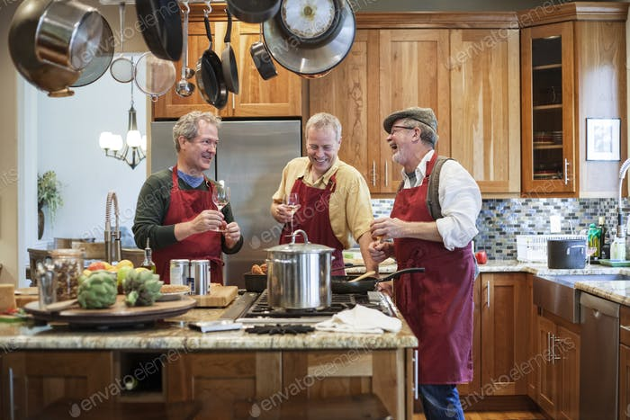 Three senior men friends cooking a meal in the kitchen.