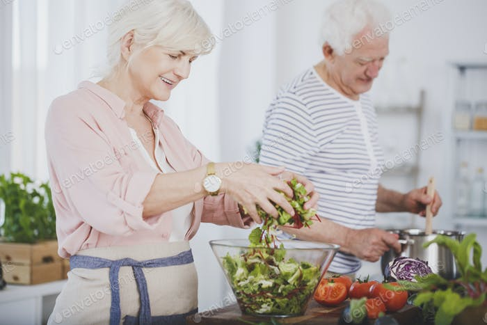 Older woman tossing a salad