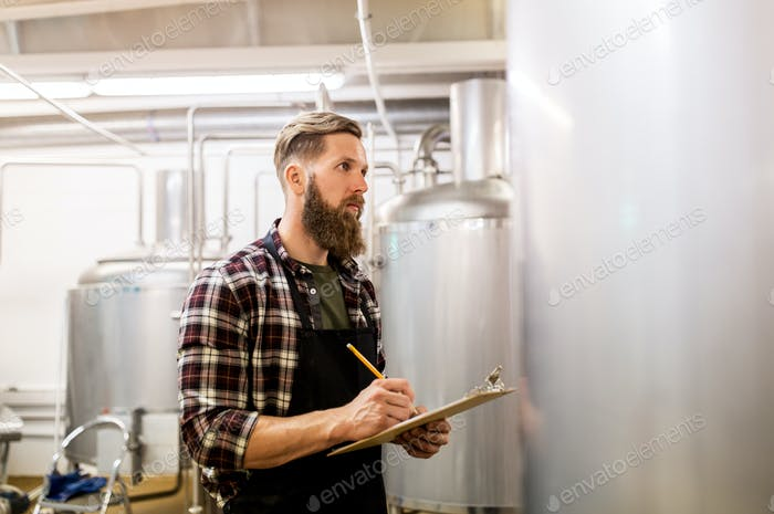 man with clipboard at craft brewery or beer plant
