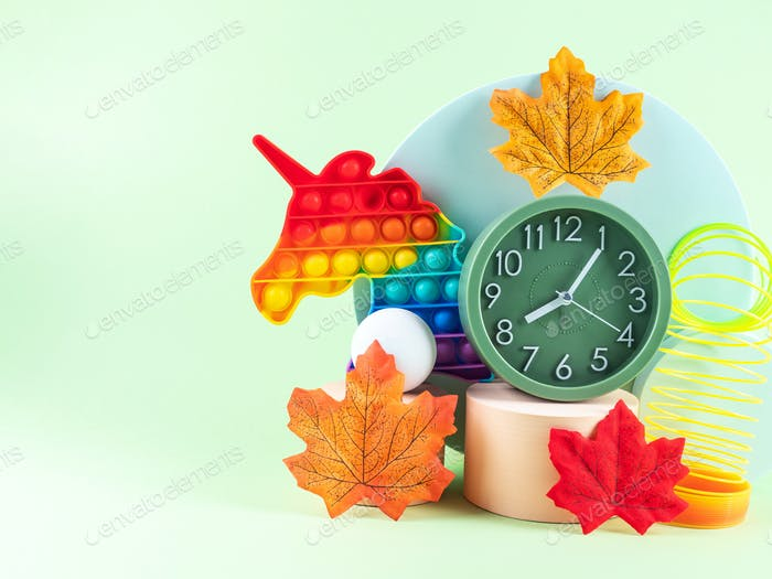 Hello autumn composition with orange leaves, geometric podiums, alarm clock and unicorn toy on green