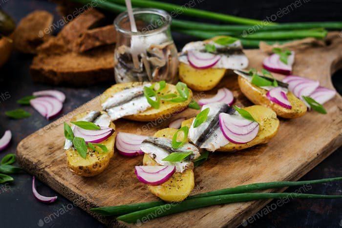 Appetizer of herring anchovy and baked potato.
