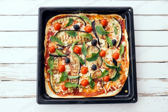 Homemade pizza with grilled egg-plant, cherry tomatoes, cheese, olives and rocket