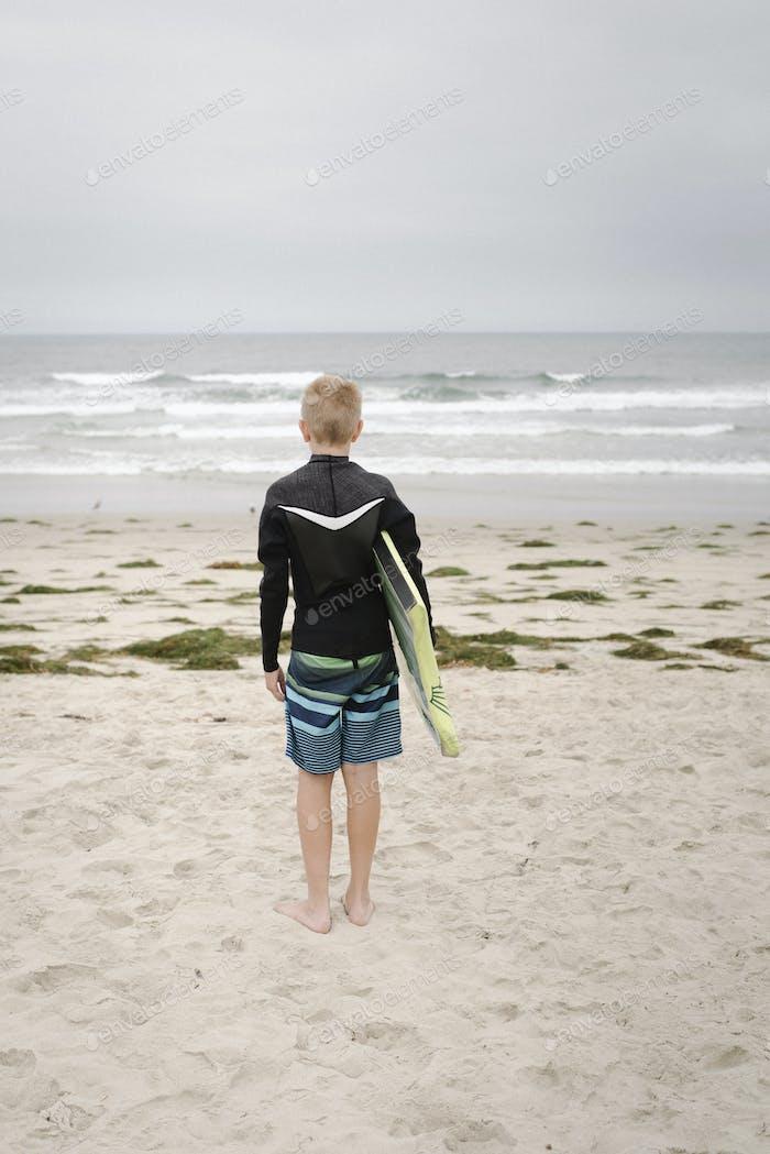 Blonder Junge, der an einem Sandstrand steht und ein Bodyboard hält.