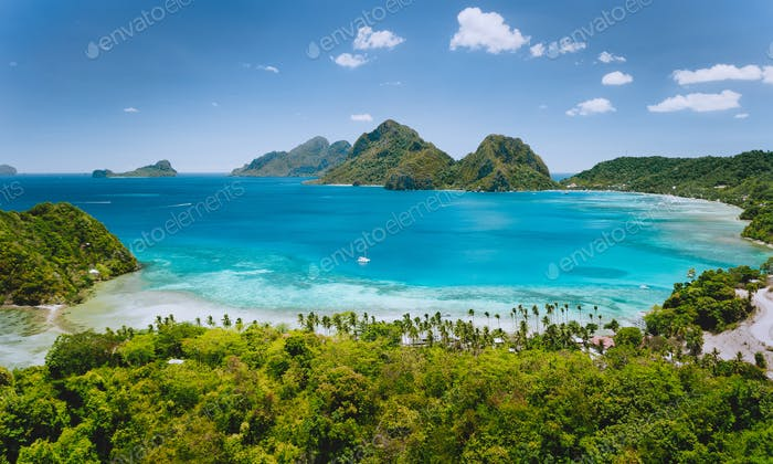 Aerial drone panoramic view of Las Cabanas beach and exotic ocean shallow lagoon in El Nido, Palawan