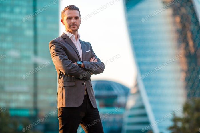 Businessman looking on copy space while standing against glass skyscraper