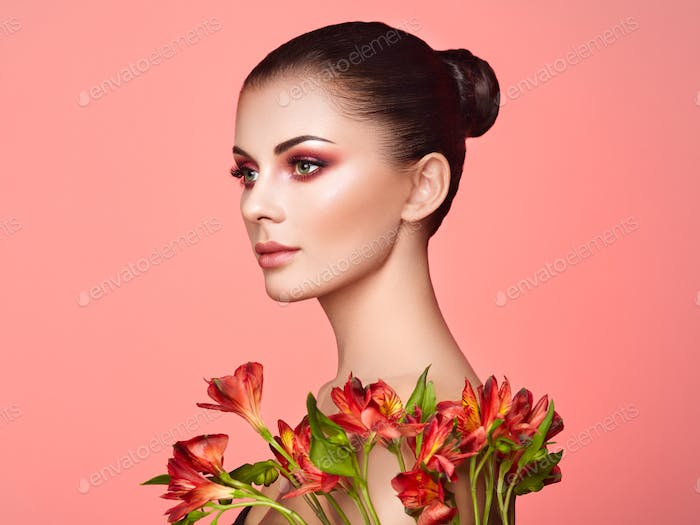 Portrait of beautiful young woman with Alstroemeria flowers