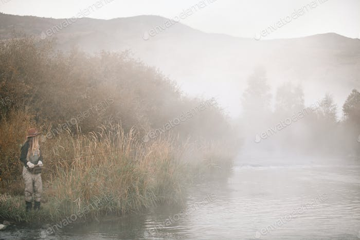 A woman fishing, standing on the riverbank. Mist rising from the water.