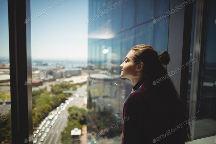 Female graphic designer looking through window