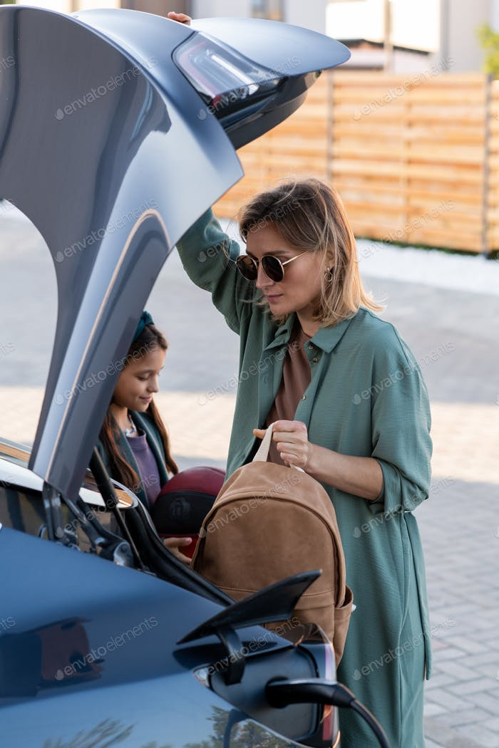 Mother and daughter taking things out of trunk while charging car