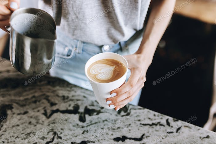 A youthful slim kind blonde girl,dressed in casual outfit,skillfully adds milk to coffee in a modern