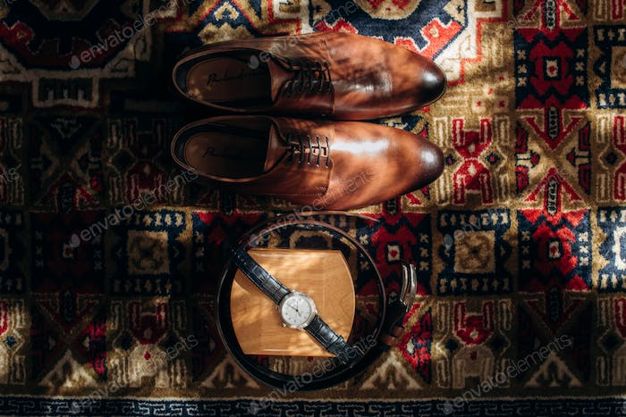 stylish watch shoes and belt view in sunlight on the floor