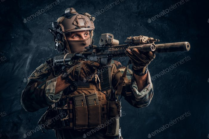 Special forces soldier in camouflage uniform holding an assault rifle with a laser sight