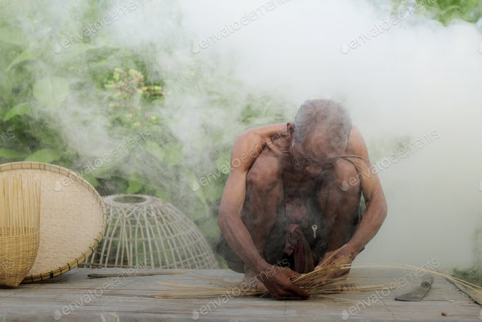 Old man are weaving basket on wooden