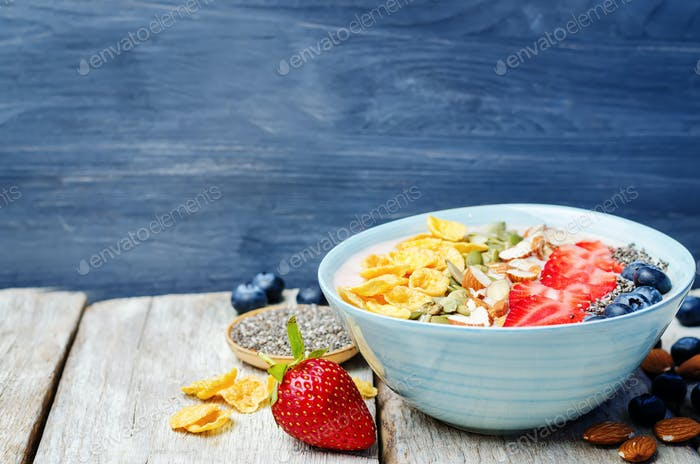 healthy strawberry smoothie bowl with fruits, cereals, seeds and